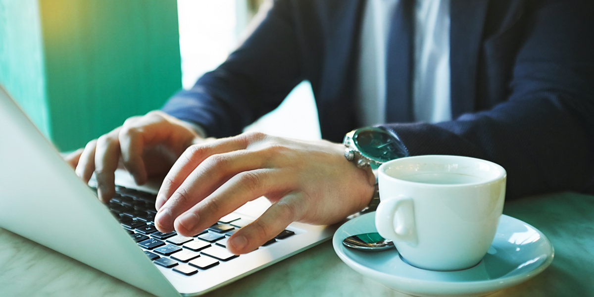 Businessman Wearing Navy Suit and Chrome Watch Using Laptop Computer Next to Empty Cup of Coffee